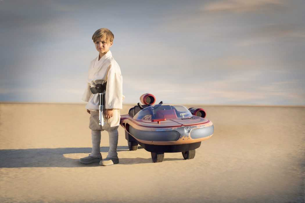 Little Boy Posing at the Side of Star Wars Luke Skywalker Landspeeder