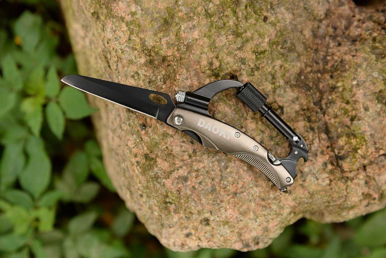 Daoki 7-in-1 Multifunctional Carabiner Placed on a Rock with Open Knife