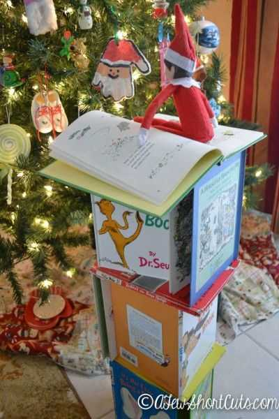 elf on a shelf - building tower of books to decorate tree