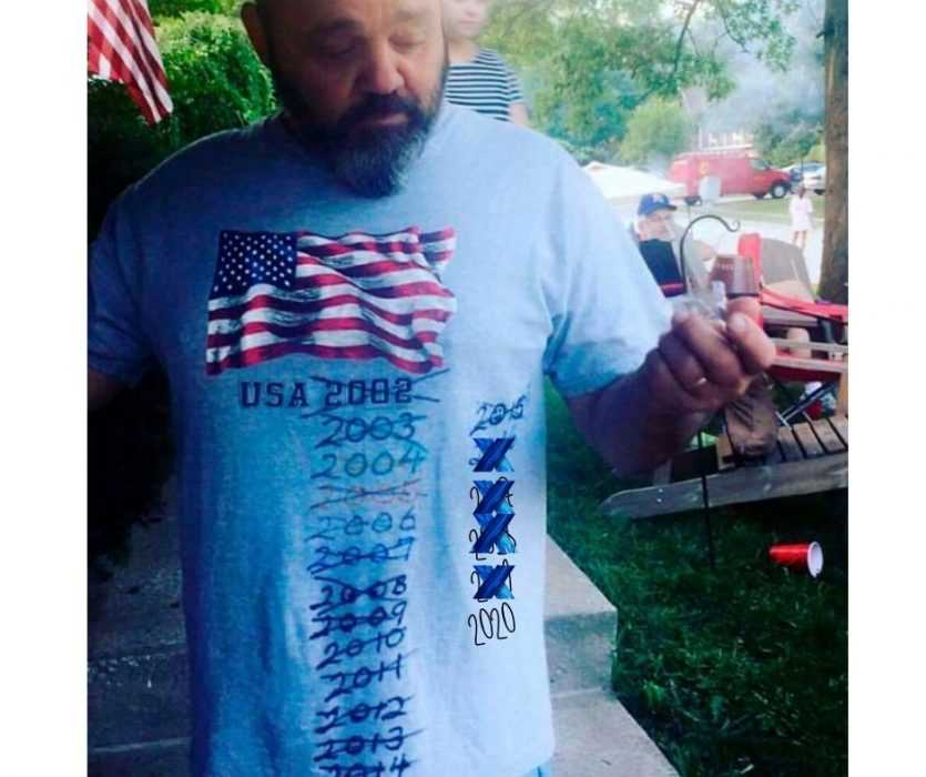 a man wearing a stars and stripes t-shirt with every year he's worn it crossed out and 2020 written at the bottom